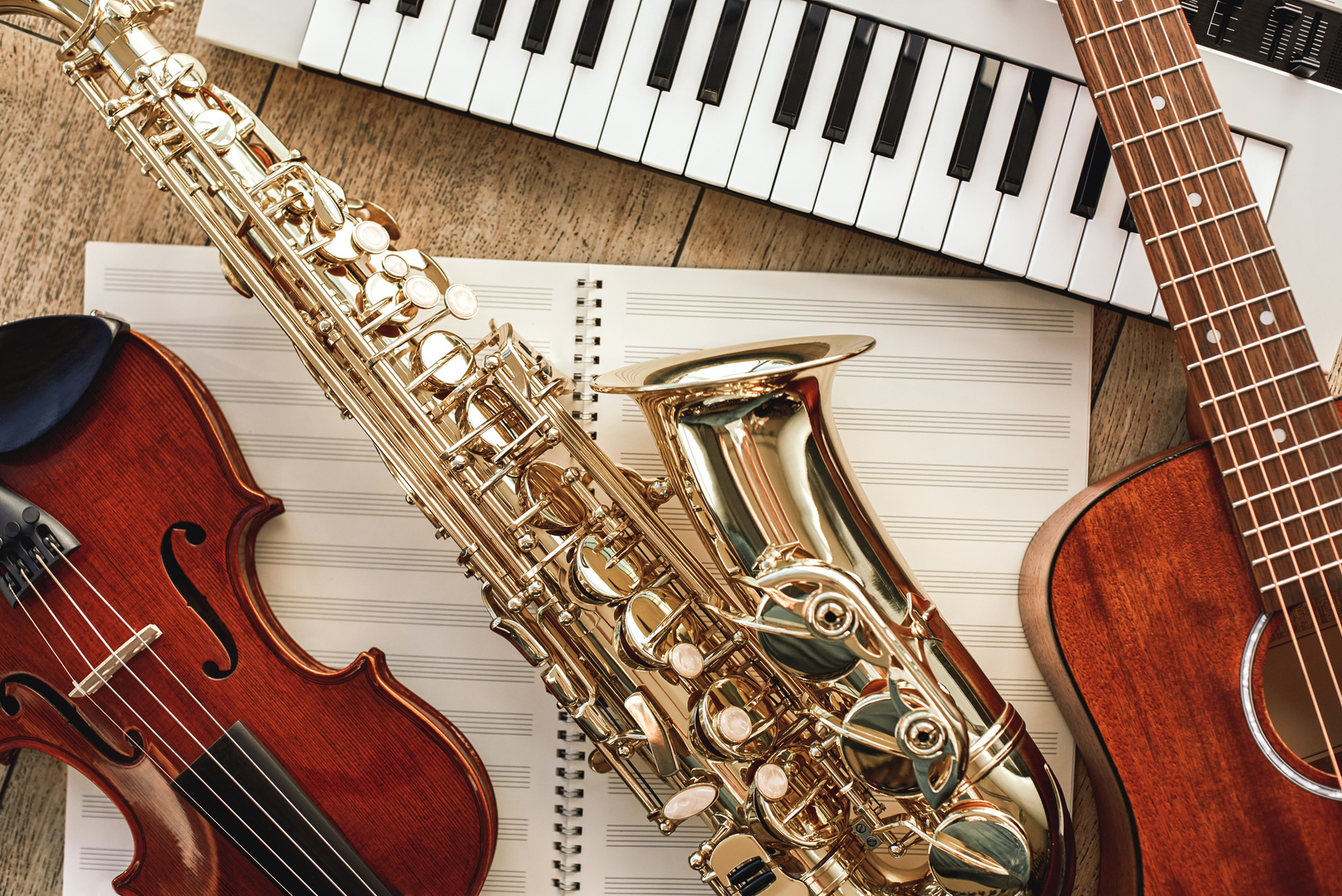 Power of music. Top view of musical instruments set: synthesizer, guitar, saxophone and violin lying on the sheets for music notes over wooden floor. Musical instruments. Music equipment